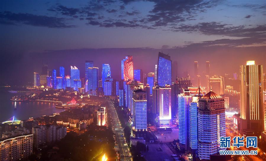 """青岛浮山湾夜景(2018年6月摄)。 办好一次会,搞活一座城。 去年6月10日,上海合作组织青岛峰会闭幕。在""""峰会效应""""的持续滋养下,青岛持续扩大开放,与上合国家的经贸往来、人文交流不断升温,城市发展注入""""上合""""动能,以崭新的面貌迎接八方来客。 新华社记者 李紫恒 摄"""